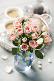 Spray roses. Romantic setup with coffee and roses in vase Stock Photos