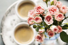 Spray roses. Romantic setup with coffee and roses in vase Royalty Free Stock Image