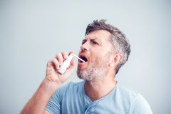 Spray for sore throat. Photo of a man who treats his throat with. A spray and sprinkles it in his mouth. The concept of health and disease Stock Photography