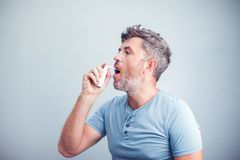 Spray for sore throat. Photo of a man who treats his throat with. A spray and sprinkles it in his mouth. The concept of health and disease Royalty Free Stock Photography