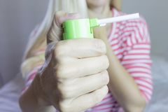 Spray for sore throat. Photo of a woman who holds spray in her hand. The concept of health and disease. Spray for sore throat. Photo of a woman who holds spray Royalty Free Stock Photography