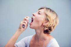 Spray for sore throat. Photo of a woman who treats her throat wi. Th a spray and sprinkles it in her mouth. The concept of health and disease Stock Images