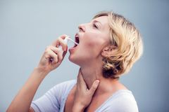 Spray for sore throat. Photo of a woman who treats her throat wi. Th a spray and sprinkles it in her mouth. The concept of health and disease Stock Image