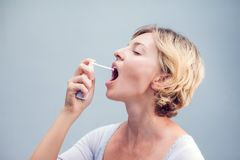 Spray for sore throat. Photo of a woman who treats her throat wi. Th a spray and sprinkles it in her mouth. The concept of health and disease Royalty Free Stock Photos