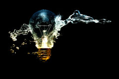 Spray of water against light bulb. On black background Stock Photos