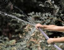 Spray water from a hose child`s hand Stock Images