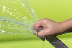 Spray water from a hose child`s hand Stock Photos