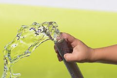 Spray water from a hose child`s hand Royalty Free Stock Image