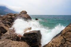 Spray from the waves on the stony shore Royalty Free Stock Photos