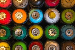 Spraycans in different colors lined up together on a table.. stock images