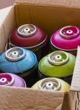 Spraydosen auf Papierkasten Stockfotografie