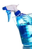 Sprayer bottle inside of measuring cup Stock Images