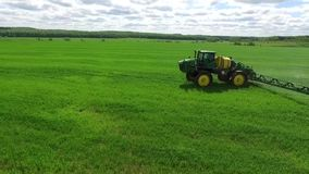 Sprayer. A tractor with a spray trailer is driving through the field. The camera overtakes him and flies over him stock footage