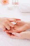 Spraying antiseptic. Close-up of manicure master spraying antiseptic on female finger Royalty Free Stock Photos