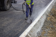 Spraying bitumen emulsion with the hand spray lance. Road worker spraying bitumen emulsion with the hand spray lance royalty free stock photography