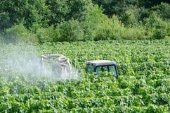 Spraying fields. Farmer spraying grape vines with tractor stock photos