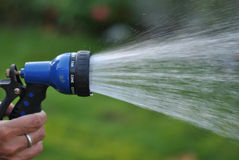 Spraying Garden Hose. This is an image of a hand holding a garden hose that is spraying water. The depth of field is used to focus on the water spray as it comes Royalty Free Stock Photo