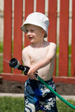 Spraying garden hose. Boy spraying garden hose on hot summer day Royalty Free Stock Image