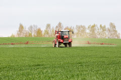Spraying the herbicides on the large green field Stock Photo