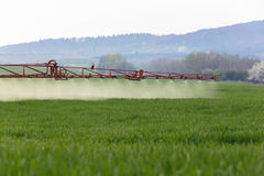 Spraying the herbicides on the large green field Stock Image