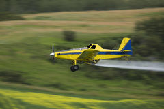 Spraying Insecticide. Crop duster spraying a crop, taken using a Panning Technique with motion blur Royalty Free Stock Images