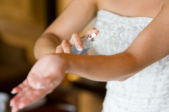 Spraying perfume. A horizontal photo in natural light of a caucasian woman spraying perfume on her wrist on her wedding day Royalty Free Stock Images