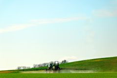 Spraying pesticide. A tractor spraying pesticide in a cultivated field stock photo