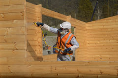 Spraying the preservative. Tradesman spray painting the wall of a wooden industrial building with timber preservative Royalty Free Stock Photography