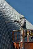 Spraying the roof. Tradesman spray painting the roof of an industrial building Royalty Free Stock Image