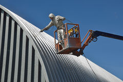 Spraying the roof. Tradesman spray painting the roof of an industrial building Royalty Free Stock Images