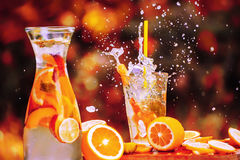 Spraying into the sides chilled summer drink in a glass. Refreshing drink in a glass cup with frutkov, slices of oranges and lemons vokurg. Splash splashes from stock photos