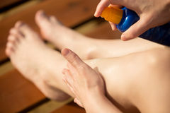 Spraying sunscreen lotion on legs. Young woman holding bottle of sunscreen lotion, applying sunblock cream on legs before tanning on wooden sun lounger, close up Stock Image