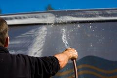 Spraying water. Man spraying water after washing his caravan Royalty Free Stock Photos