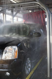 Spraying water on automobile in car wash Royalty Free Stock Images