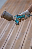 Spraying wood deck with spray gun Royalty Free Stock Photography