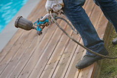 Spraying wood deck with spray gun stock photography