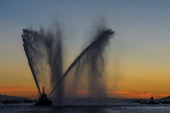 Sprays water as firefighter boat. A floating modern tug boat sprays jets of water, demonstrates firefighting water cannon, sprays water as firefighter boat with Stock Image