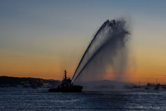 Sprays water as firefighter boat. A floating modern tug boat sprays jets of water, demonstrates firefighting water cannon, sprays water as firefighter boat with Royalty Free Stock Photos