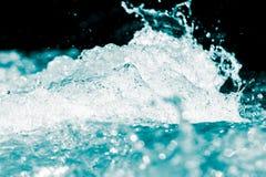 Spraywasser auf einem schwarzen Hintergrund Stockfotos