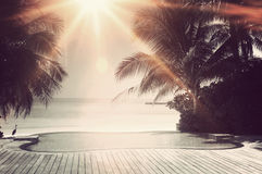 Sprazzo di sole luminoso sopra uno stagno di lusso di infinito Fotografia Stock Libera da Diritti