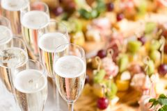Furshet. Table top full of glasses of sparkling white wine with canapes and antipasti in the background. champagne. Spread of alcoholic beverages for celebration royalty free stock images