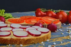 Spread butter on bread with sliced tomatoes and radishes. Fresh snack on natural wooden background.  Stock Image