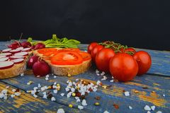 Spread butter on bread with sliced tomatoes and radishes. Fresh snack on natural wooden background.  Royalty Free Stock Photography