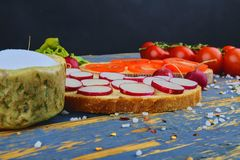Spread butter on bread with sliced tomatoes and radishes. Fresh snack on natural wooden background.  Royalty Free Stock Images