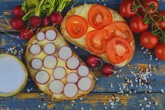 Spread butter on bread with sliced tomatoes and radishes. Fresh snack on natural wooden background. Flat design. Top. View Stock Images
