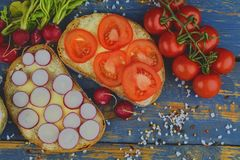 Spread butter on bread with sliced tomatoes and radishes. Fresh snack on natural wooden background. Flat design. Top. View Royalty Free Stock Image