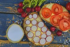 Spread butter on bread with sliced tomatoes and radishes. Fresh snack on natural wooden background. Flat design. Top. View Royalty Free Stock Photography