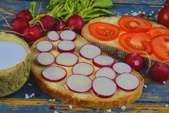 Spread butter on bread with sliced tomatoes and radishes. Fresh snack on natural wooden background. Flat design. Top. View Stock Photo