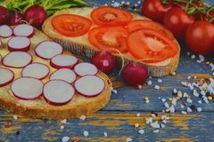Spread butter on bread with sliced tomatoes and radishes. Fresh snack on natural wooden background. Flat design. Top. View Royalty Free Stock Photo