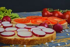 Spread butter on bread with sliced tomatoes and radishes. Fresh snack on natural wooden background.  Royalty Free Stock Image